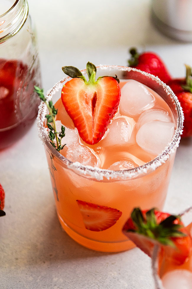 Strawberry margarita on a white table, garnished with a sprig of thyme and half of a fresh strawberry.