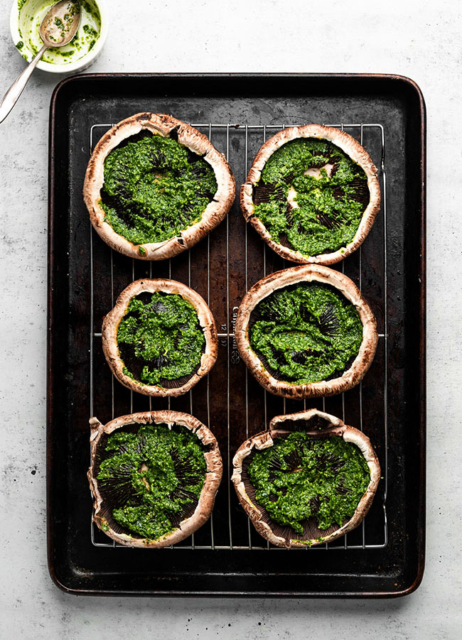 Six mushroom caps on a baking sheet, each filled with a layer of bright green pesto.