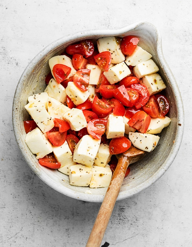 Wooden spoon stirring tomatoes and mozzarella in a large grey bowl.