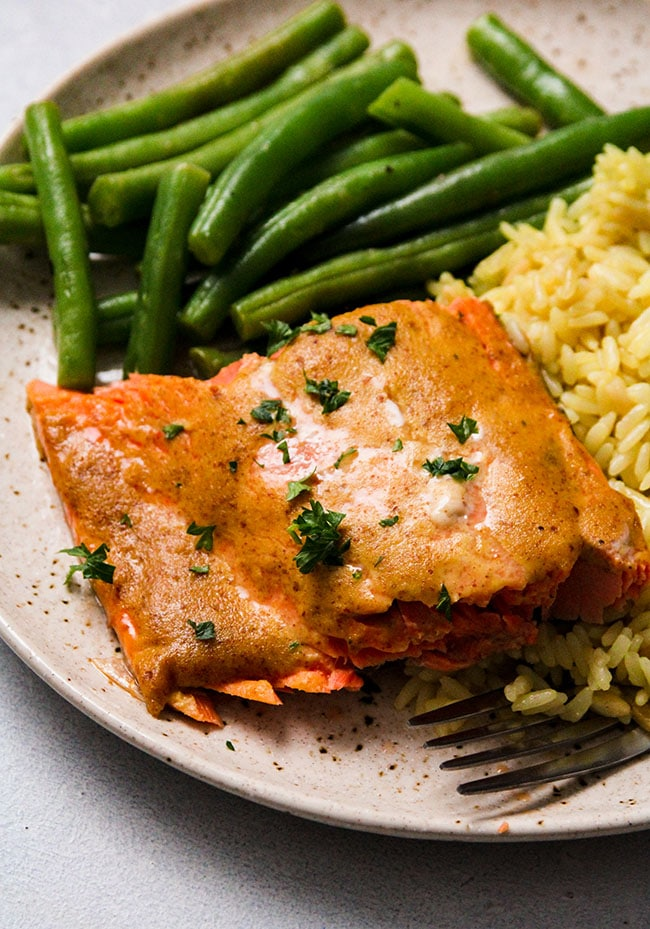 A piece of mustard salmon on a plate with green beans and rice pilaf.