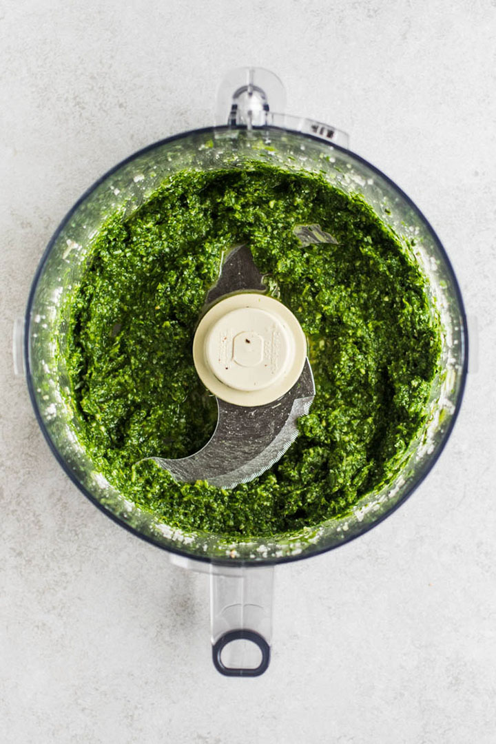 Pesto in the bowl of a food processor, on a white table.