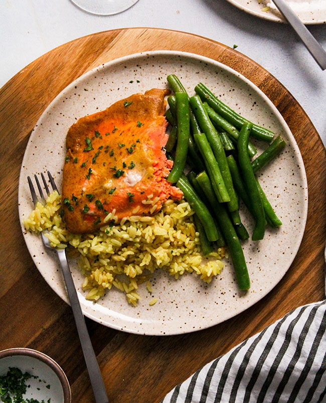 Overhead view of a piece of mustard salmon on a tan plate with green beans and rice.