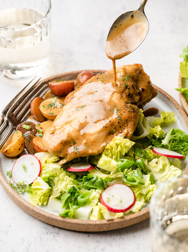 Spoon drizzling mustard sauce over a chicken breast, on a white plate next to a green salad.