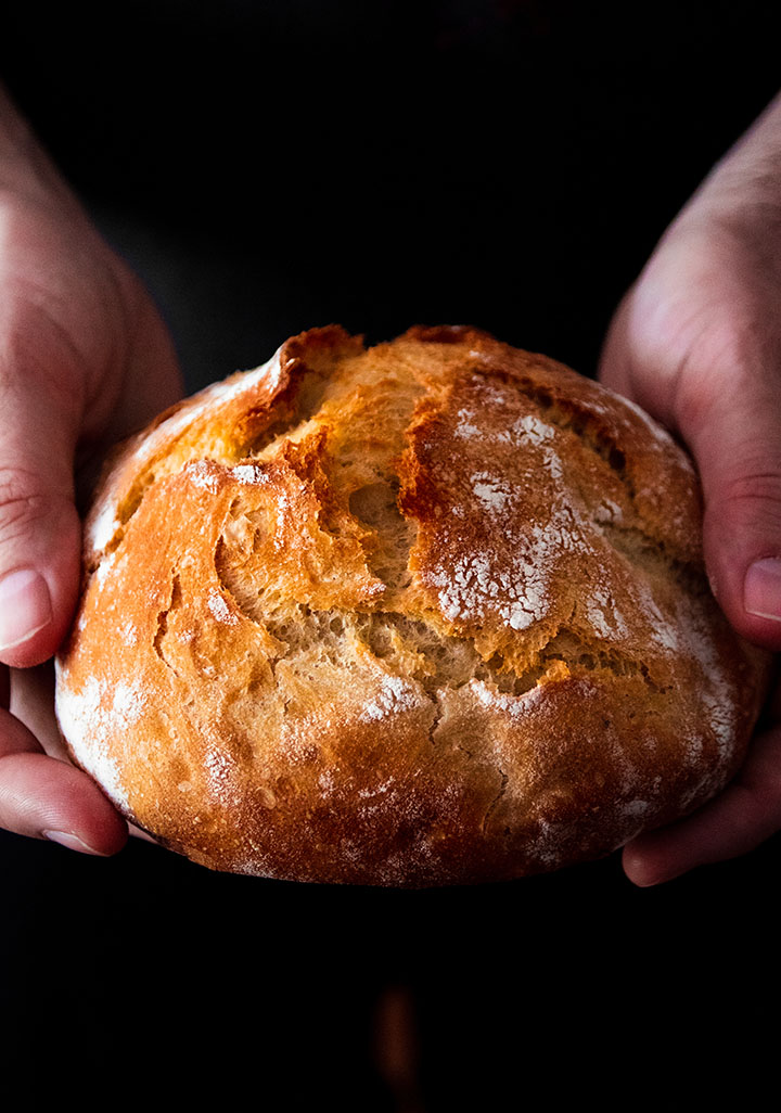 Hands holding a small loaf of bread.