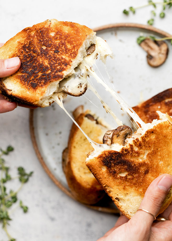 Hands pulling two halves of a grilled cheese sandwich apart as melted mozzarella stretches out.
