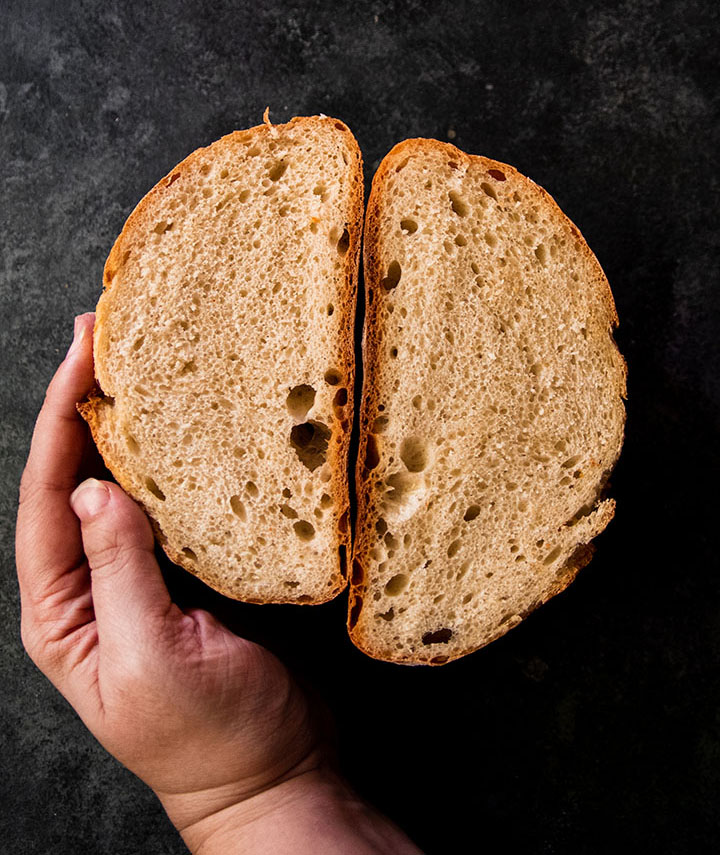 Hand holding two halves of a small loaf of bread.