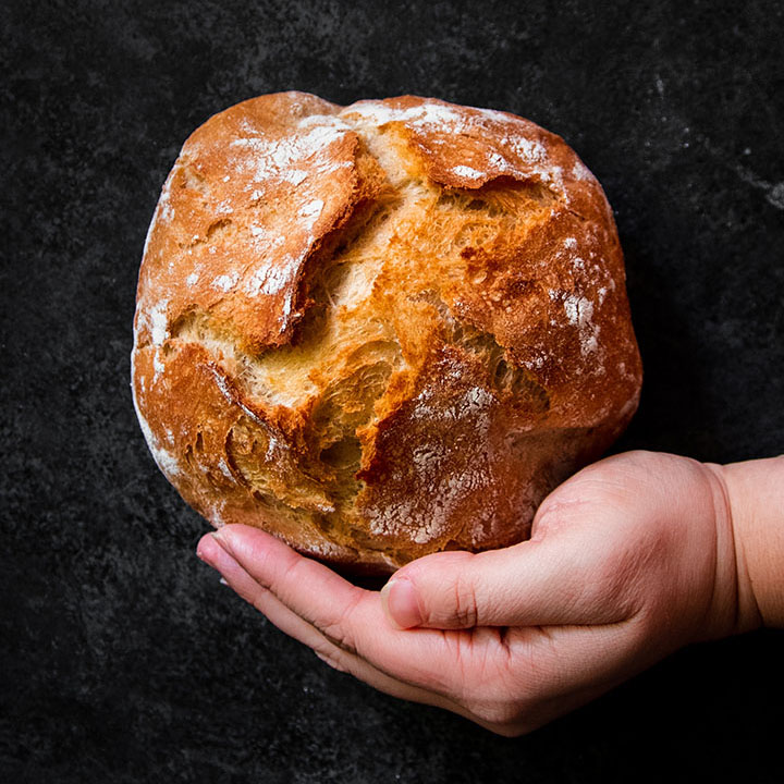 Hand holding a small loaf of bread in front of a black background.
