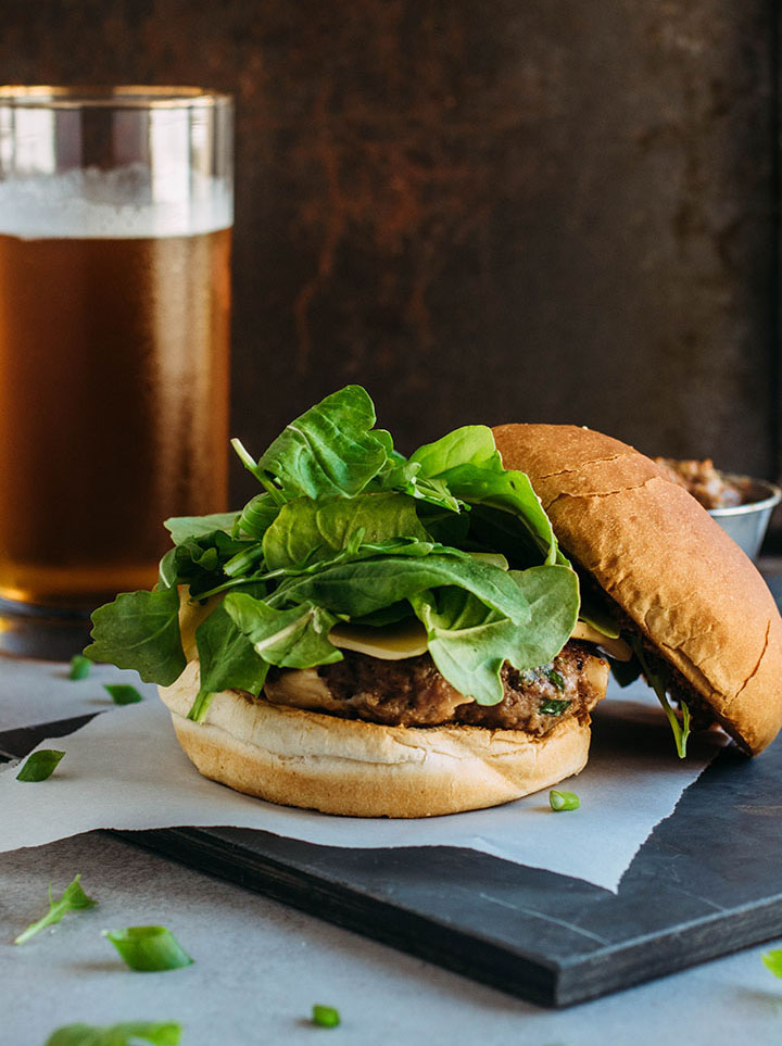 Cheeseburger topped with fresh arugula, with the top bun off to the side.