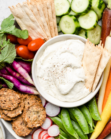 Whipped feta in a small bowl surrounded by brightly colored fresh vegetables.