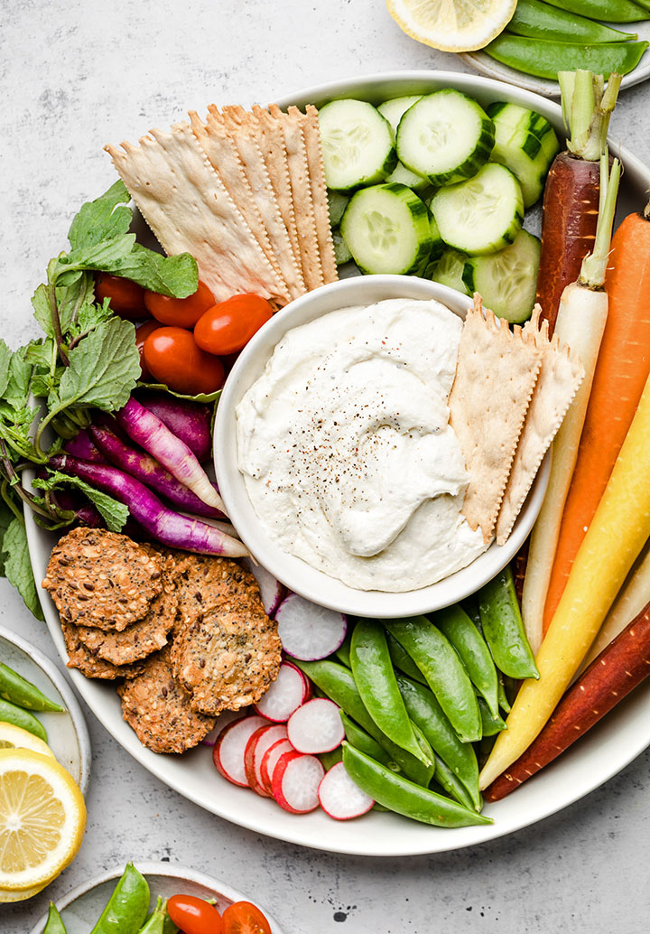 Whipped feta cheese in a small white bowl, surrounded by bright vegetables.
