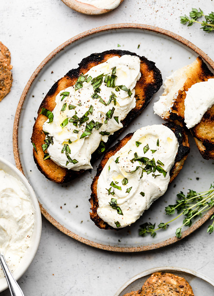 Grilled bread topped with whipped feta, olive oil, and fresh basil.