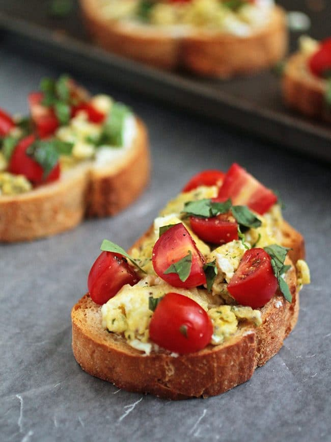 Toast topped with scrambled eggs, cherry tomato, and fresh basil.