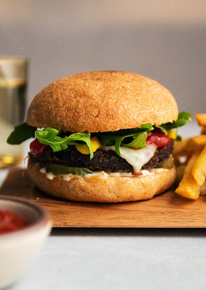 Black bean burger on a whole wheat bun, sitting on top of a wooden serving plate next to a pile of french fries.