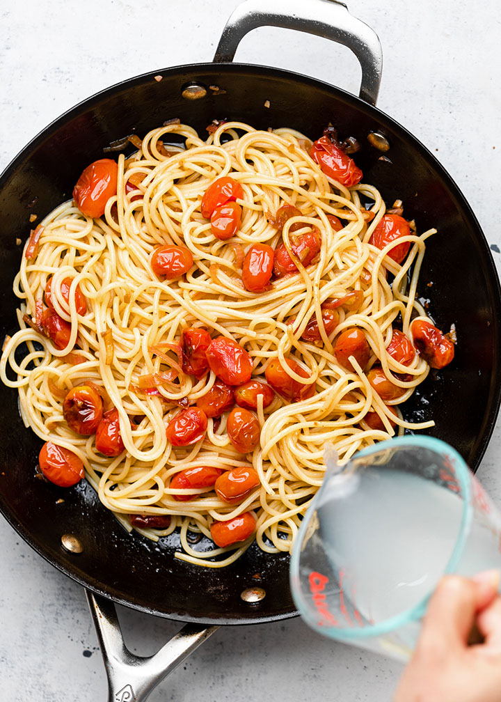 Hand pouring a splash of pasta water into the skillet with the spaghetti.