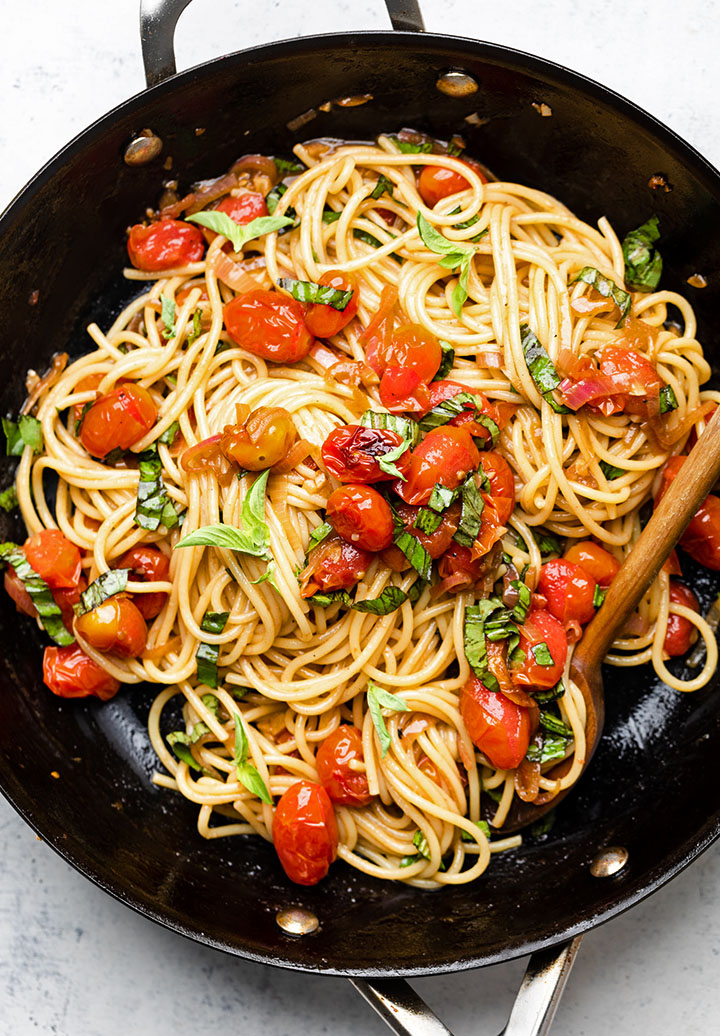 Wooden spoon stirring spaghetti and tomatoes in a black skillet.