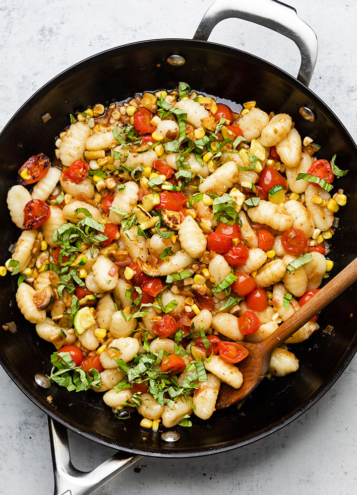 Wooden spoon stirring gnocchi with veggies in a large black skillet.