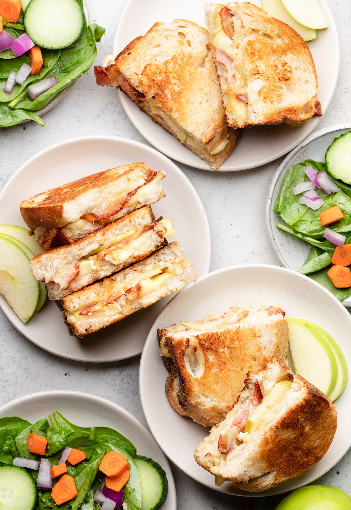 Three grilled cheese sandwiches on small white plates, next to small bowls of green salad.
