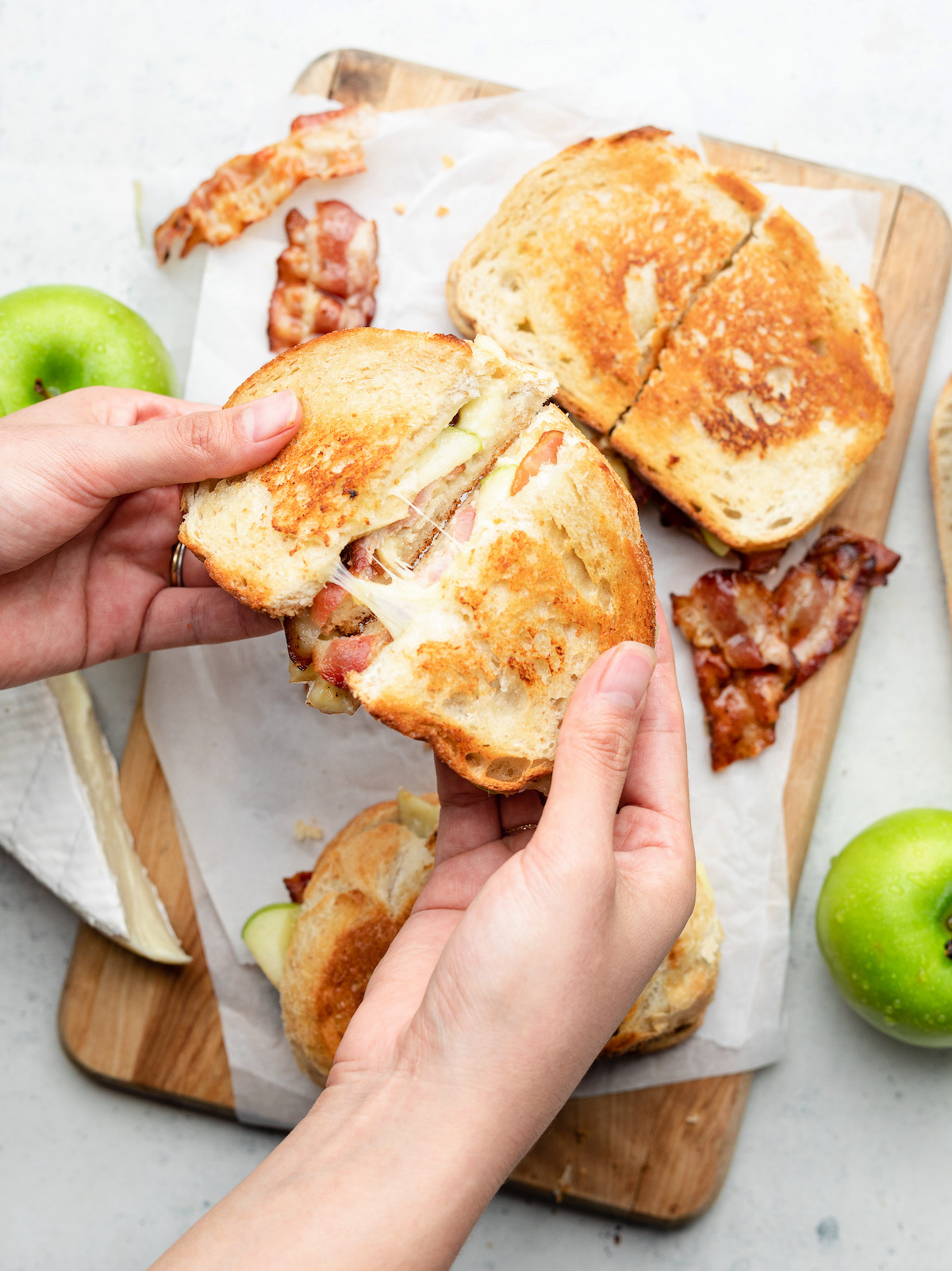 Hands pulling two halves of a grilled cheese sandwich apart.