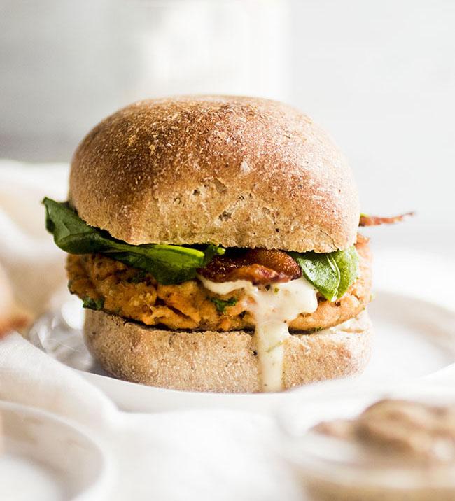 Salmon burger with a wheat bun on a white plate.