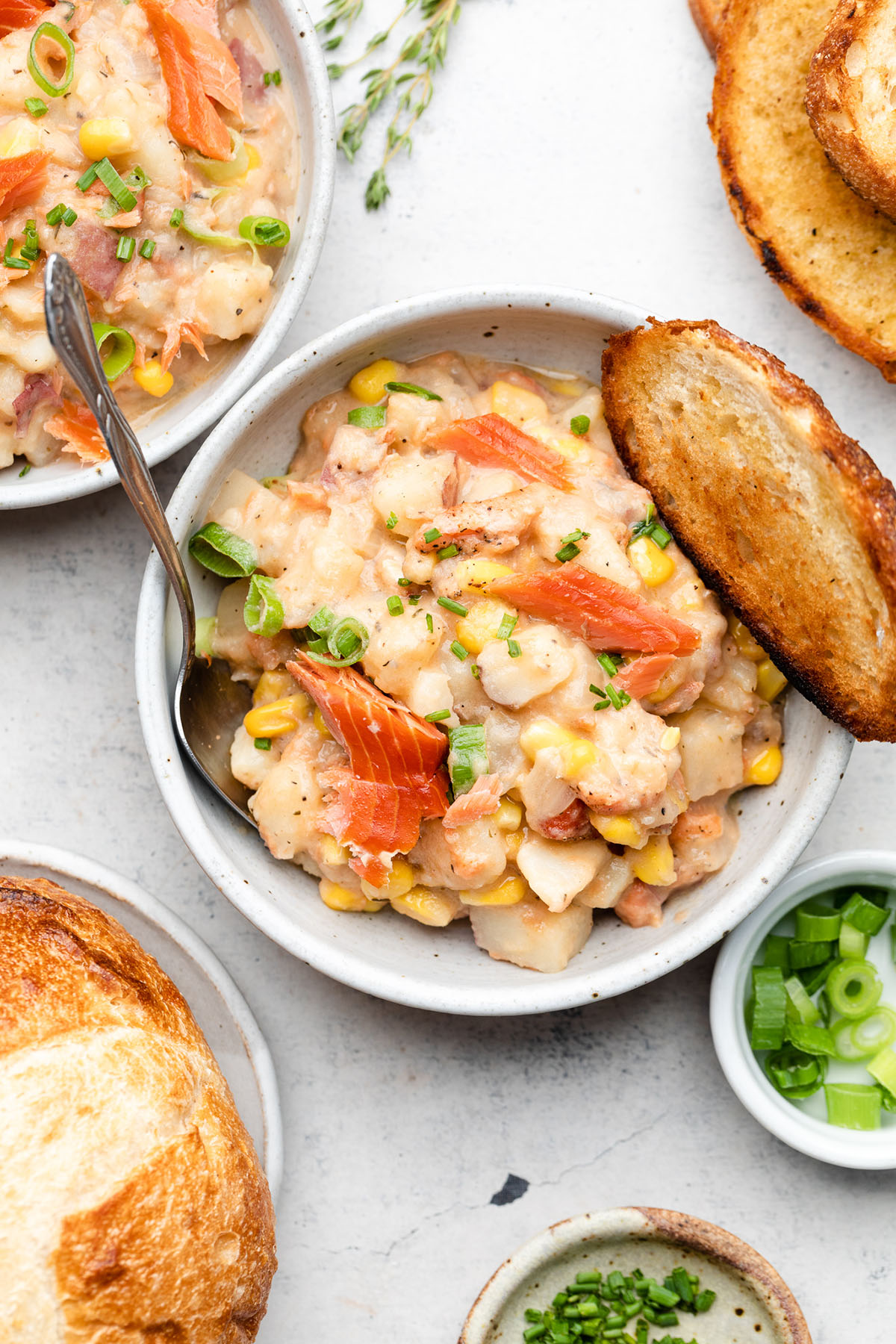 Chowder in a white bowl with a silver spoon and a piece of toasted bread.