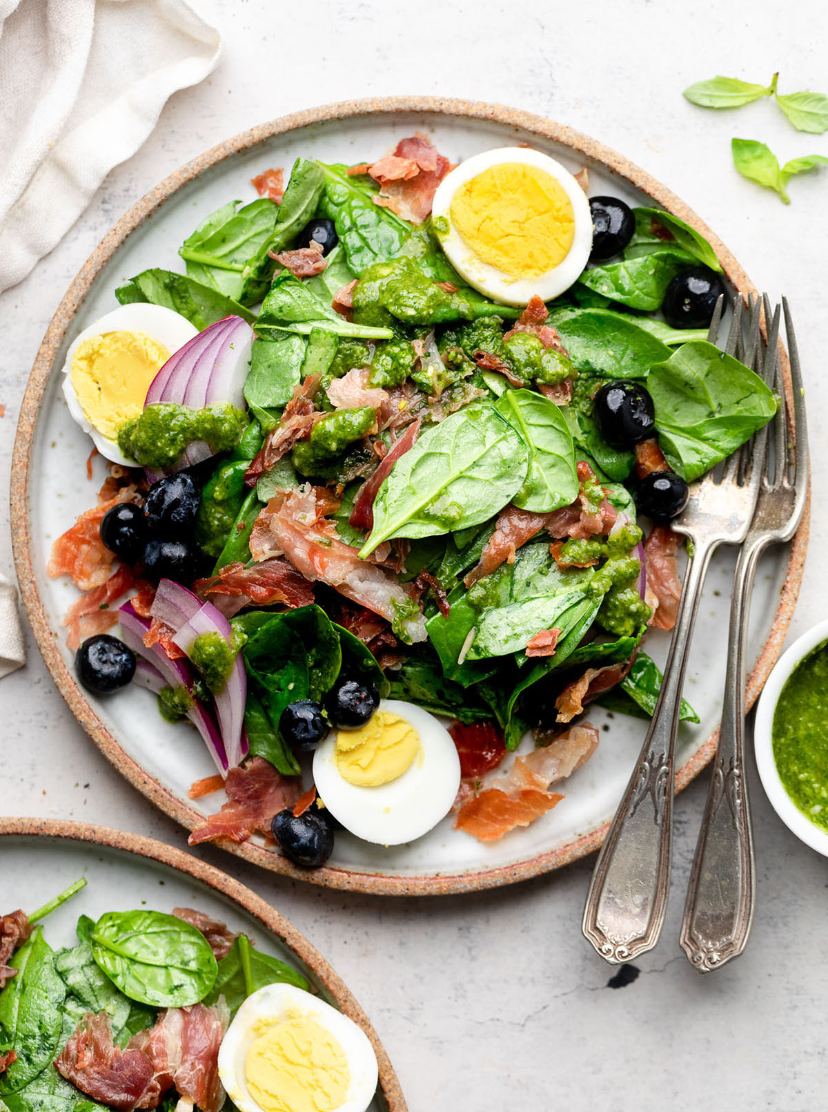 Salad topped with hard boiled eggs, red onion, and blueberries.