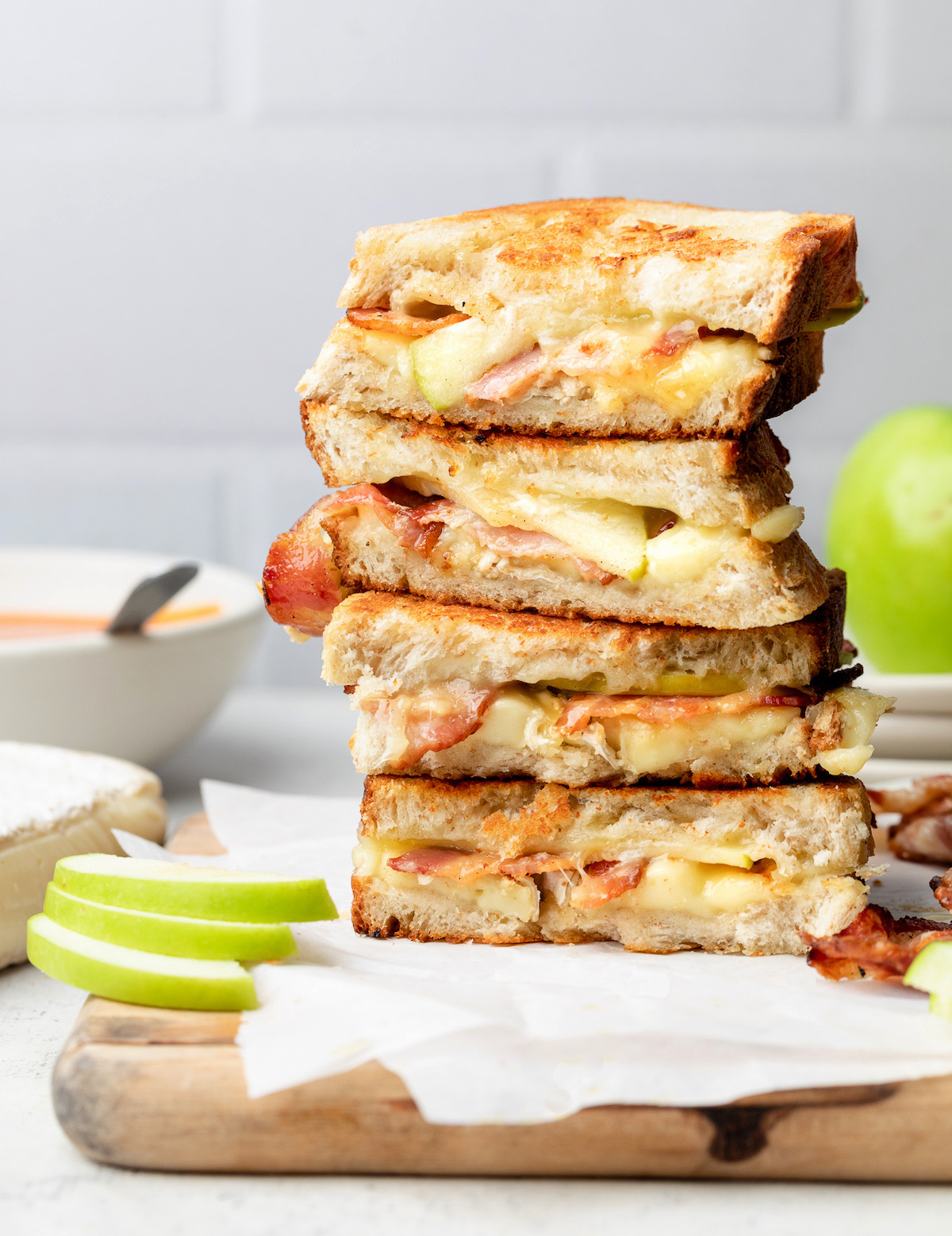 A stack of sandwiches on a wooden cutting board in front of a white surface.