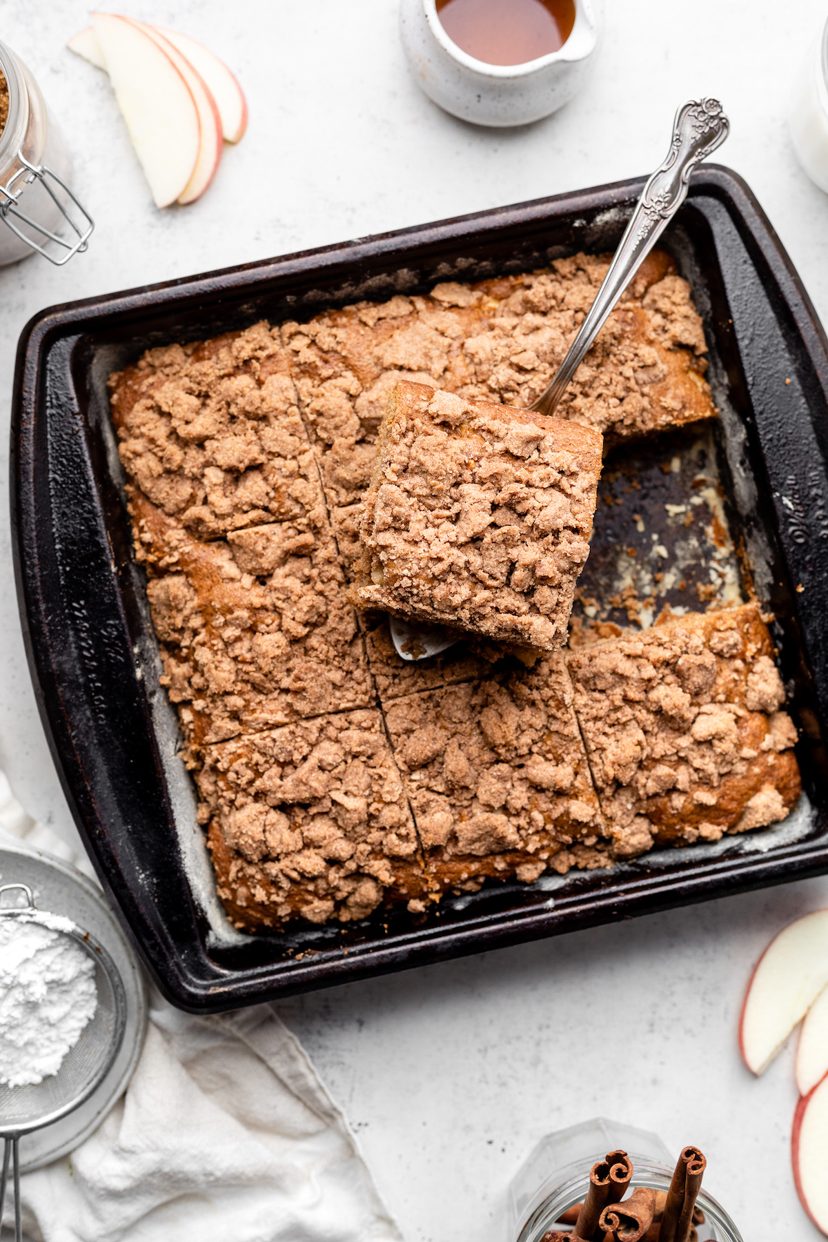 Silver serving spoon lifting a slice of coffee cake out of a dark baking pan.