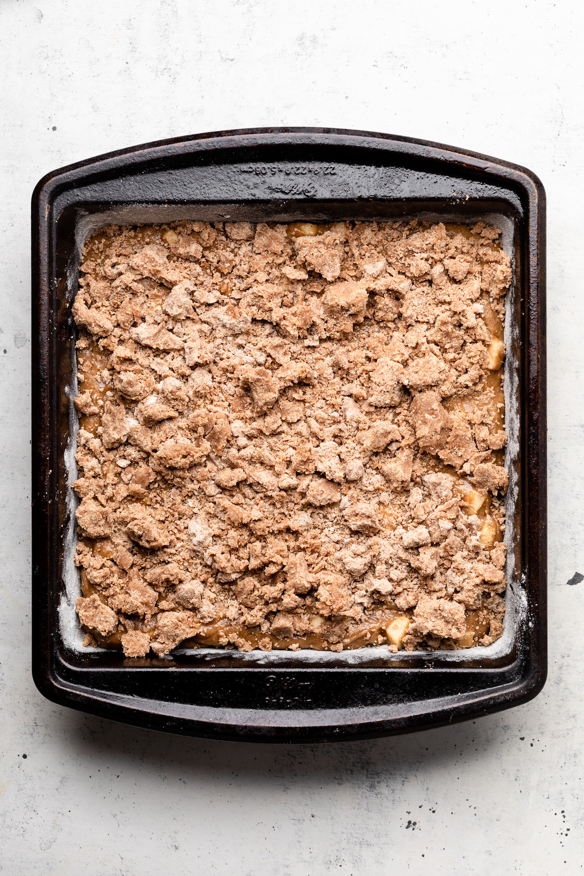 Coffee cake batter in a dark, square baking dish, topped with crumble topping.