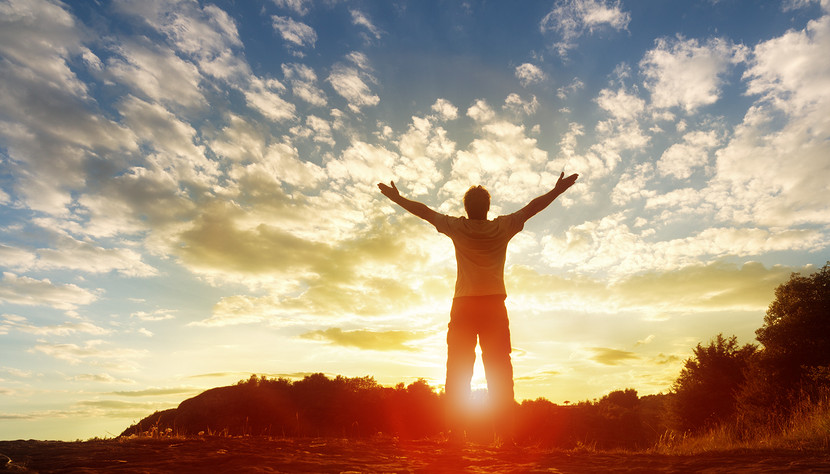 Silhouette of a man with hands raised in the sunset concept for