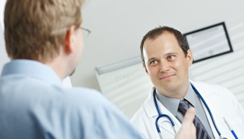 Medical office - smiling male doctor and patient talking.
