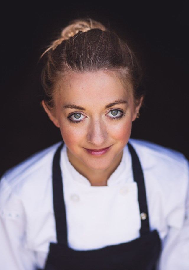 A woman dressed in chef outfit looking at the camera