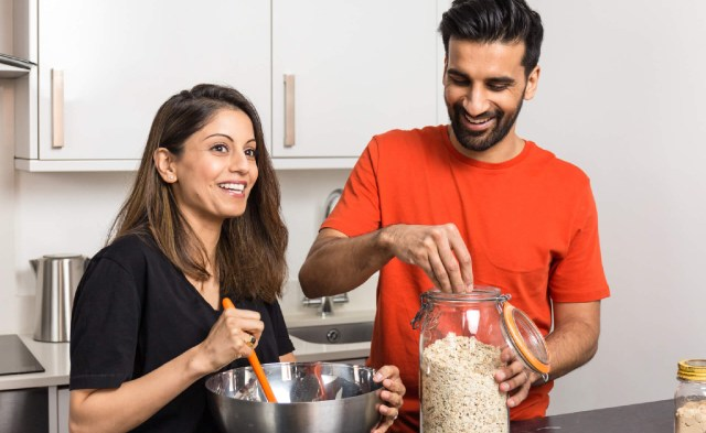 A woman and man cooking together and smiling
