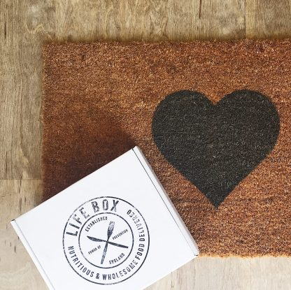 Lifebox sitting on a doormat with a heart on it