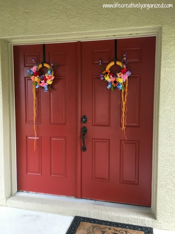 How to make a wreath for $5. Finished wreaths hung on front doors.