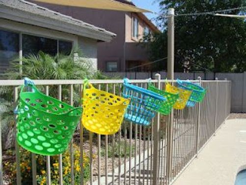 Awesome pool storage ideas - baskets hung on fence