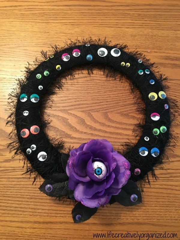 Do you feel you're being watched? This easy DIY Halloween wreath covered in googly eyes is sure to add a spooky touch to your front door. It's a real treat!