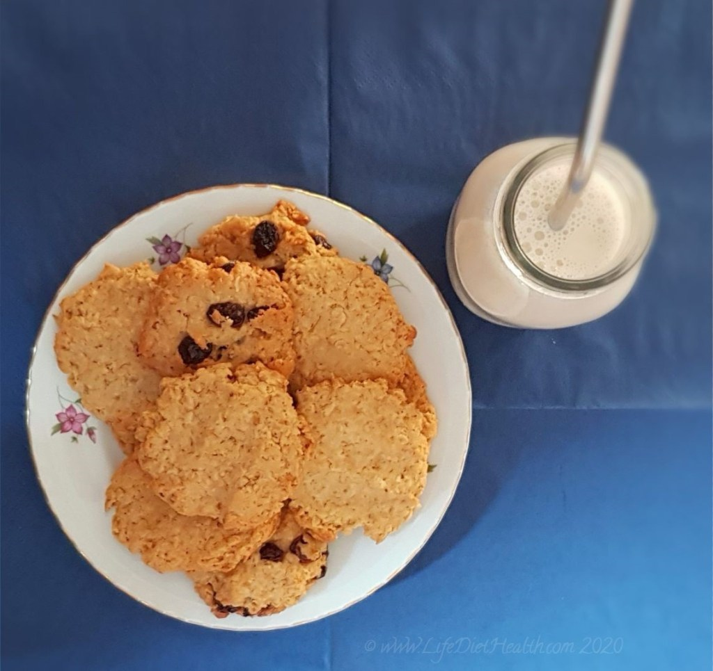 Plate of cookies with a bottle of milk and a stainless steel straw on a navy blue background.
