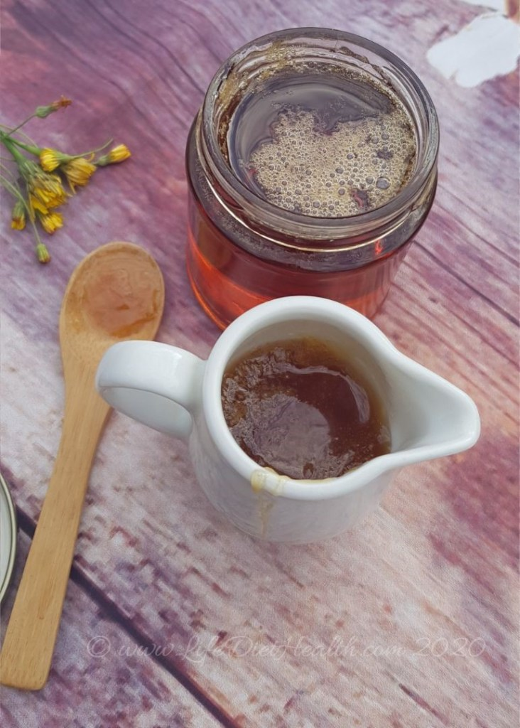 Jar of Dandelion honey - syrup and a small white jug full too. Wooden spoon and dandelion flowers in the background.