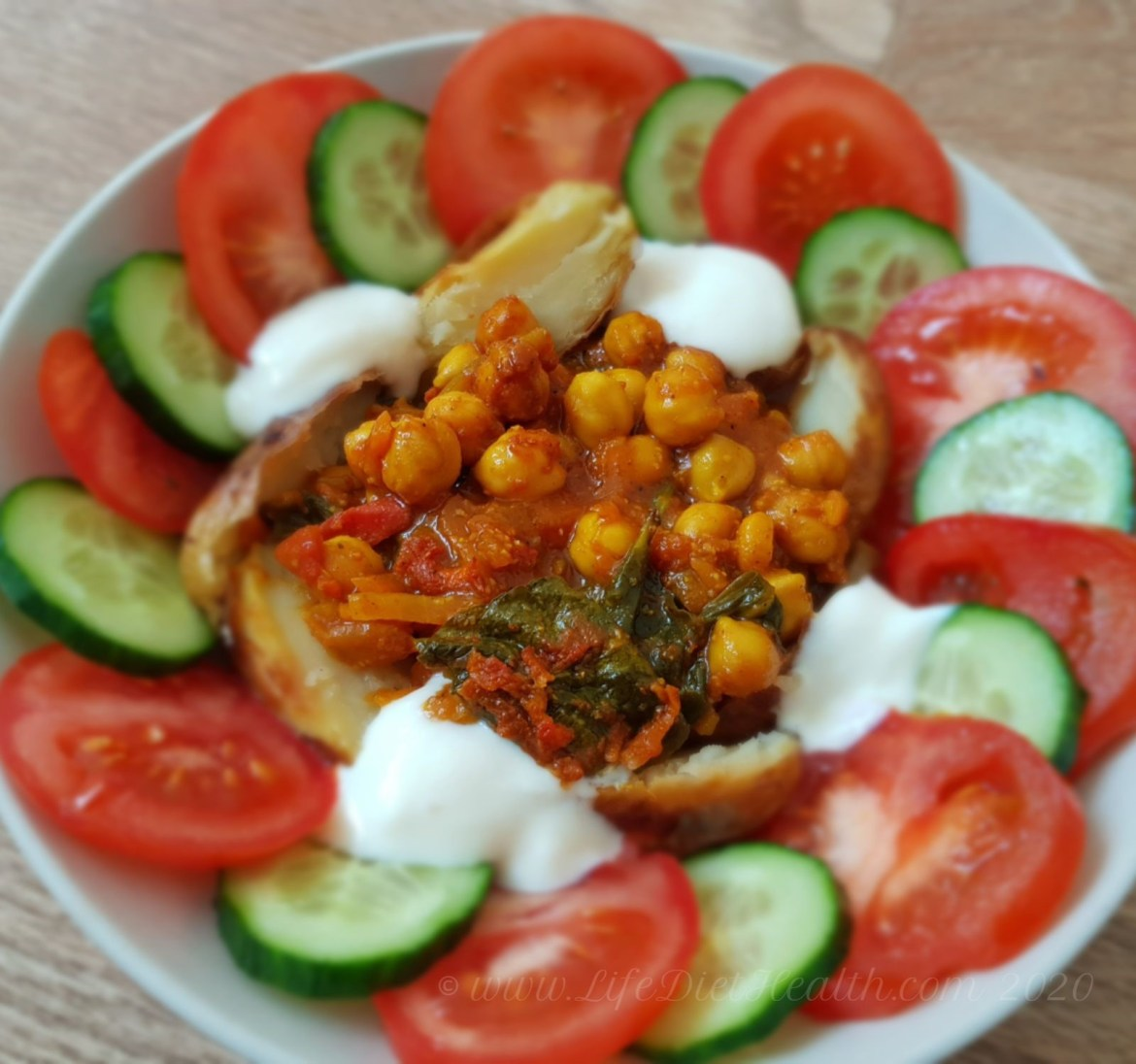 Chickpea curry in a white bowl with baked potato, cucumber and tomato rings and yogurt.