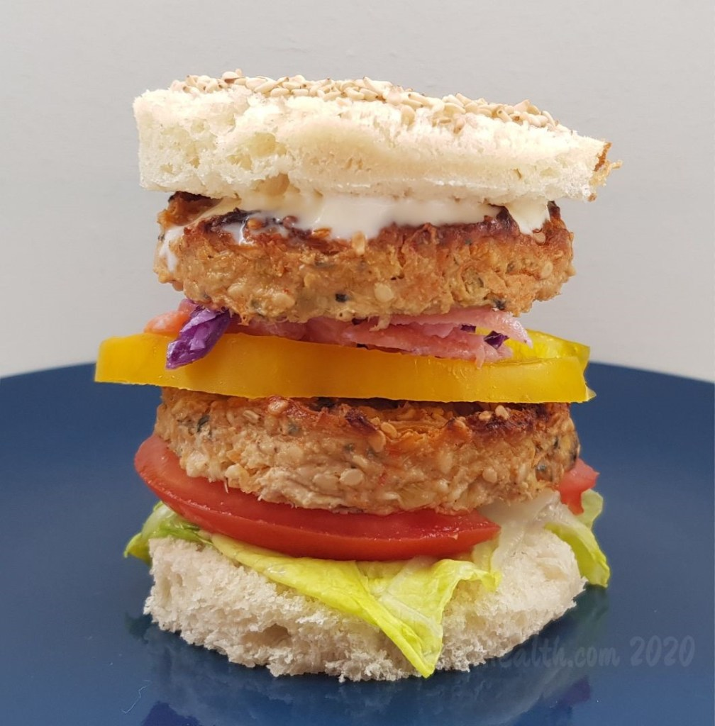 Two vegan burgers stacked with salad on a skinny white bun.