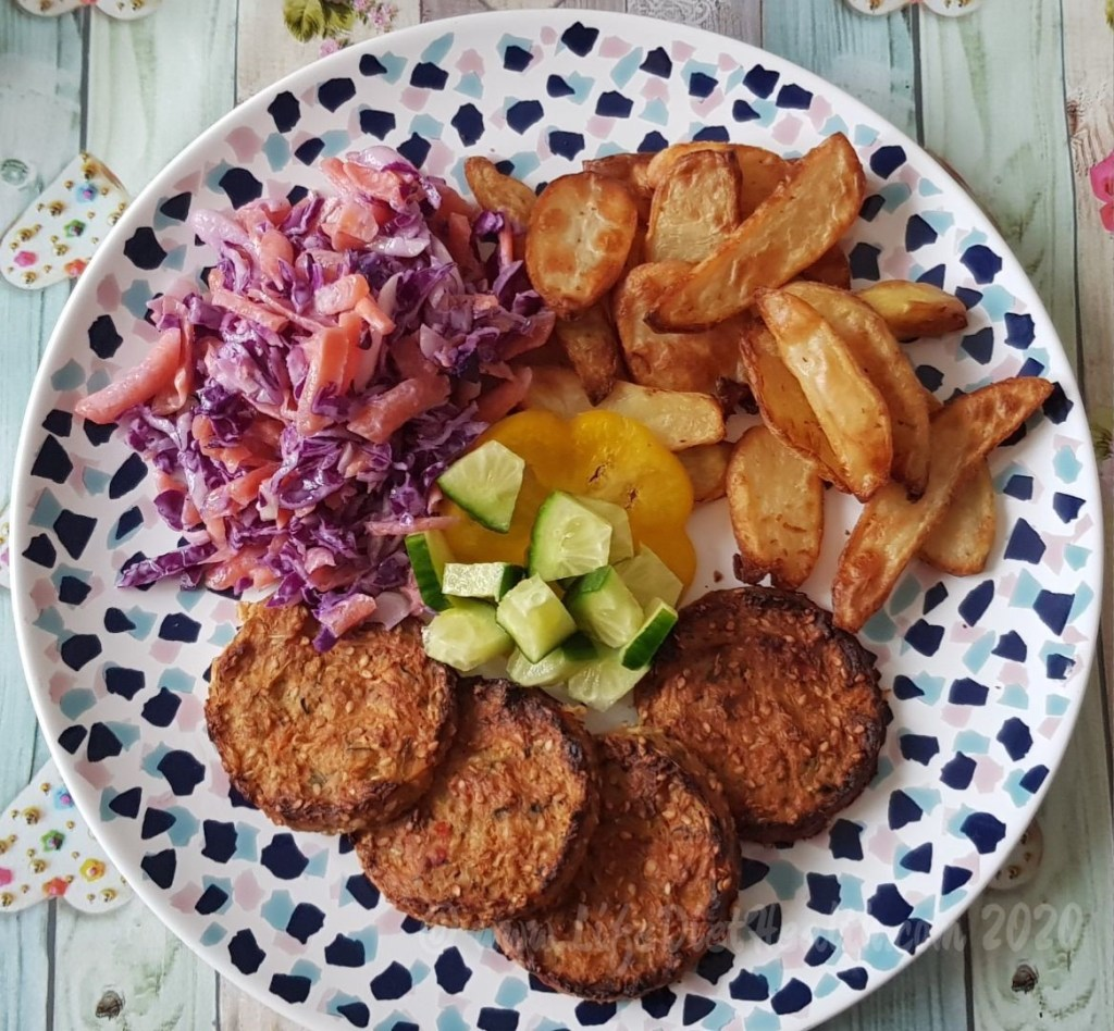 Naked Vegan burgers on a mosaic plate with potato wedges, coleslaw and salad.