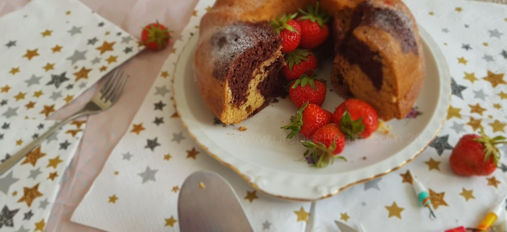 Cut marbled bundt cake with gold and silver star serviettes.