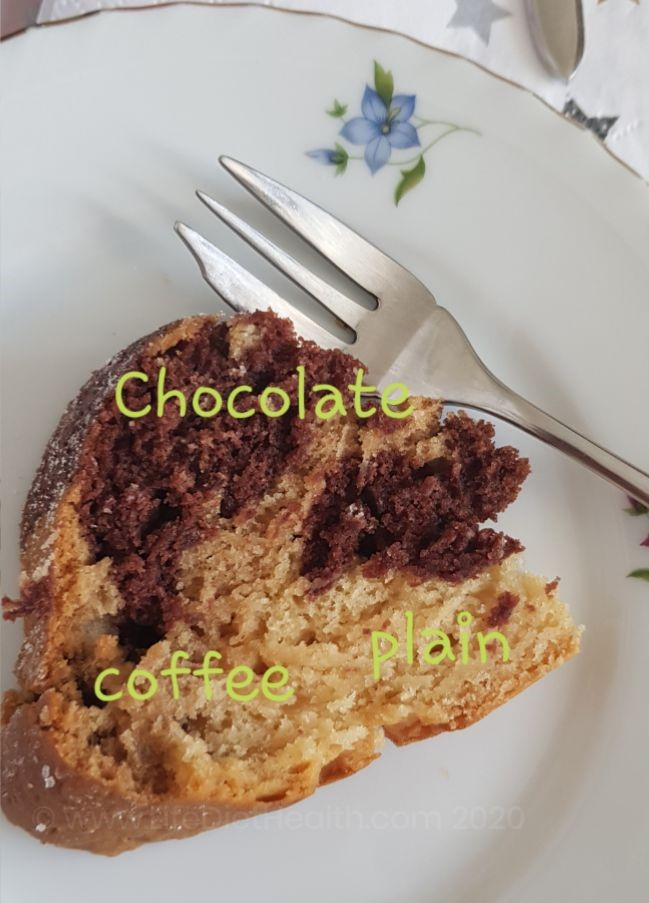 Slice of marbled bundt cake on a white china plate with a fork. Cake labelled with chocolate, coffee and plain.