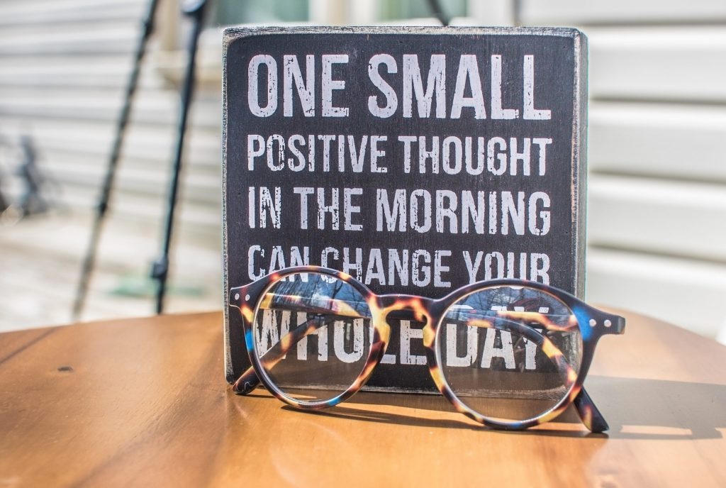 Table with a pair of glasses and a sign saying one small positive thought in the morning can change your whole day.