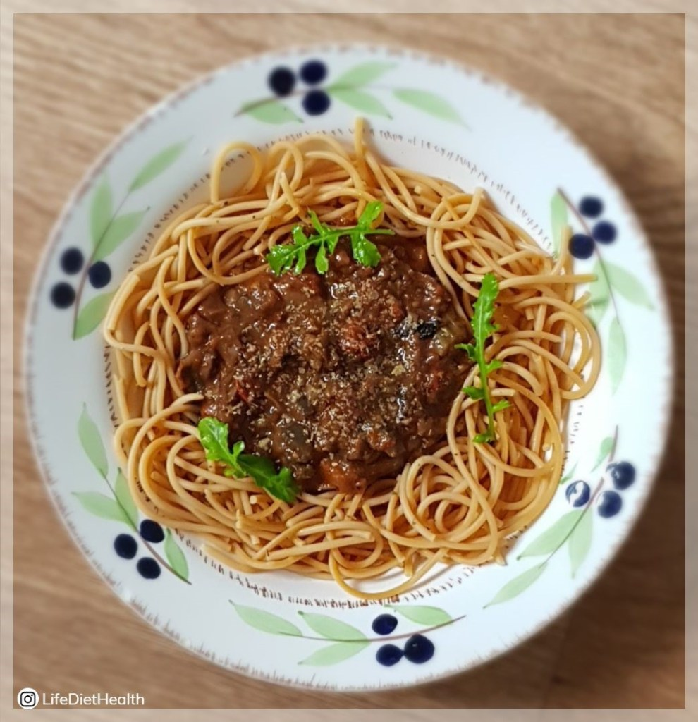 Spaghetti in a bowl with bolognese in the centre decorated with fresh rocket leaves.