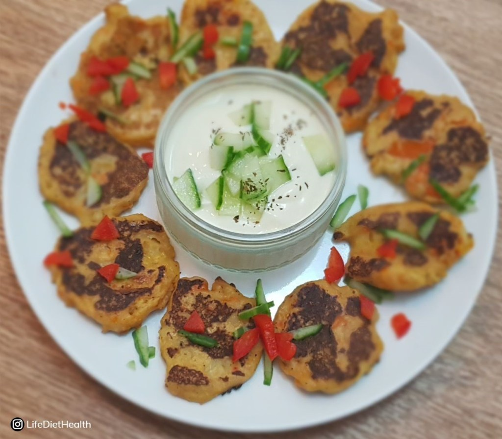 Fritters on a white plate with pot of dip