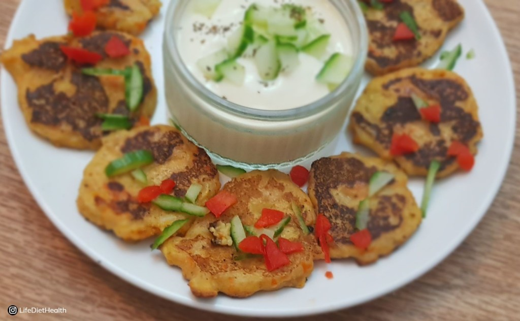 Vegetable fritters on a plate with yogurt dip, red peppers and cucumber decoration