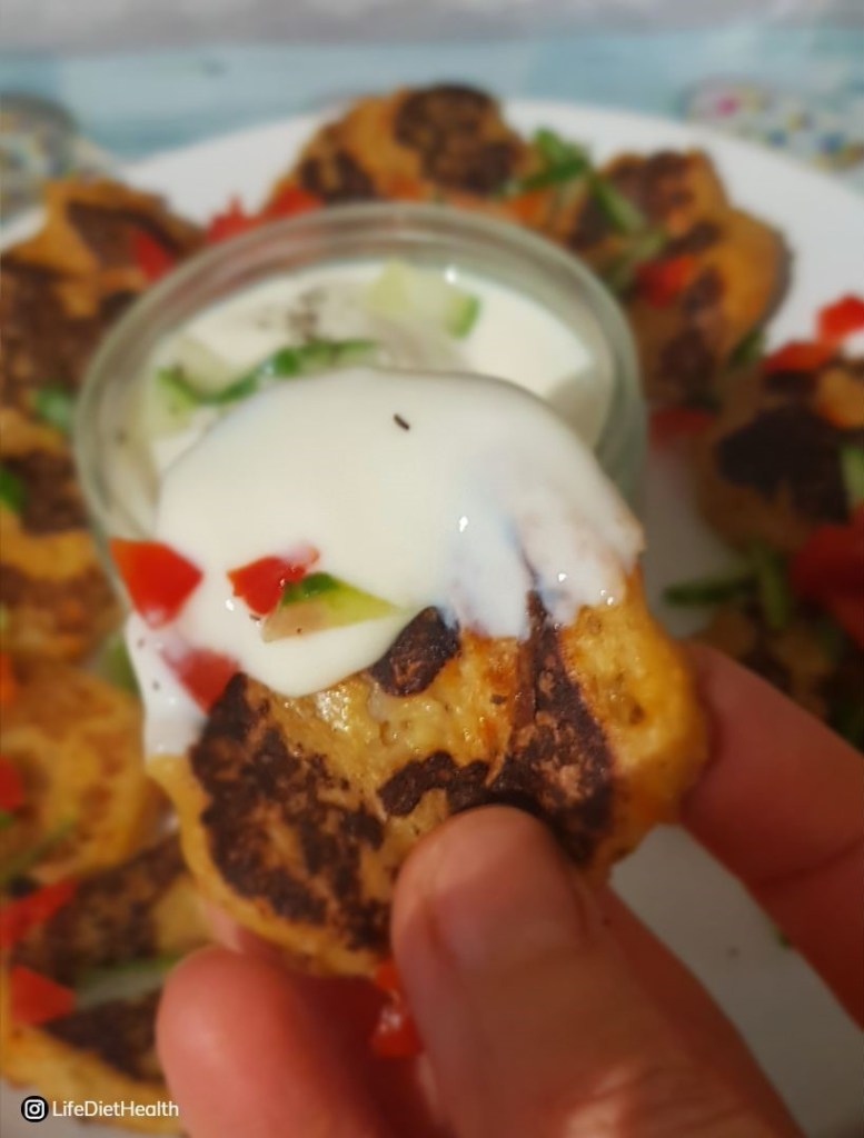Close up fritter with yogurt dip. Plate of fritters in background.