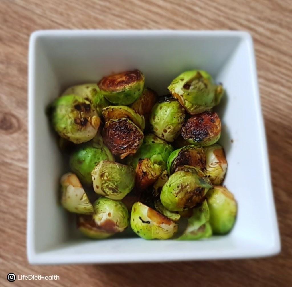 Square white bowl full of crispy glazed brussel sprouts
