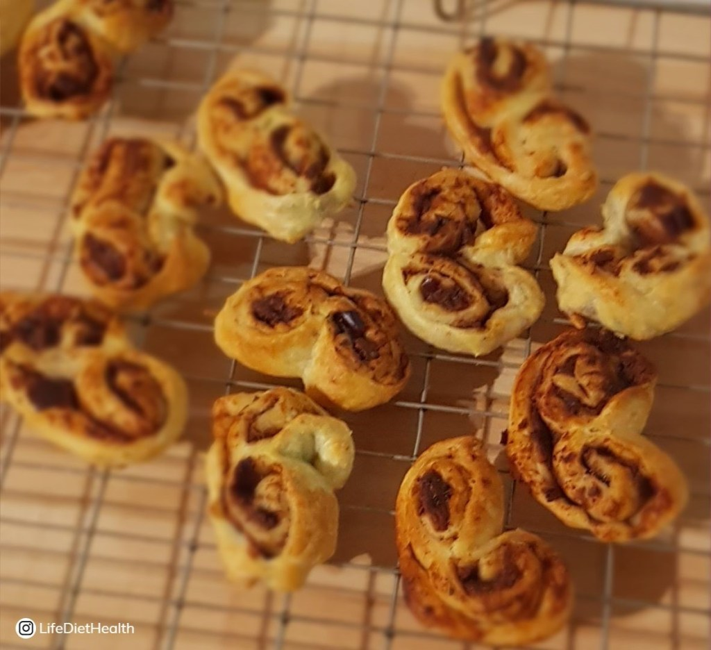 Wire rack full of cinnamon pastry palmiers.